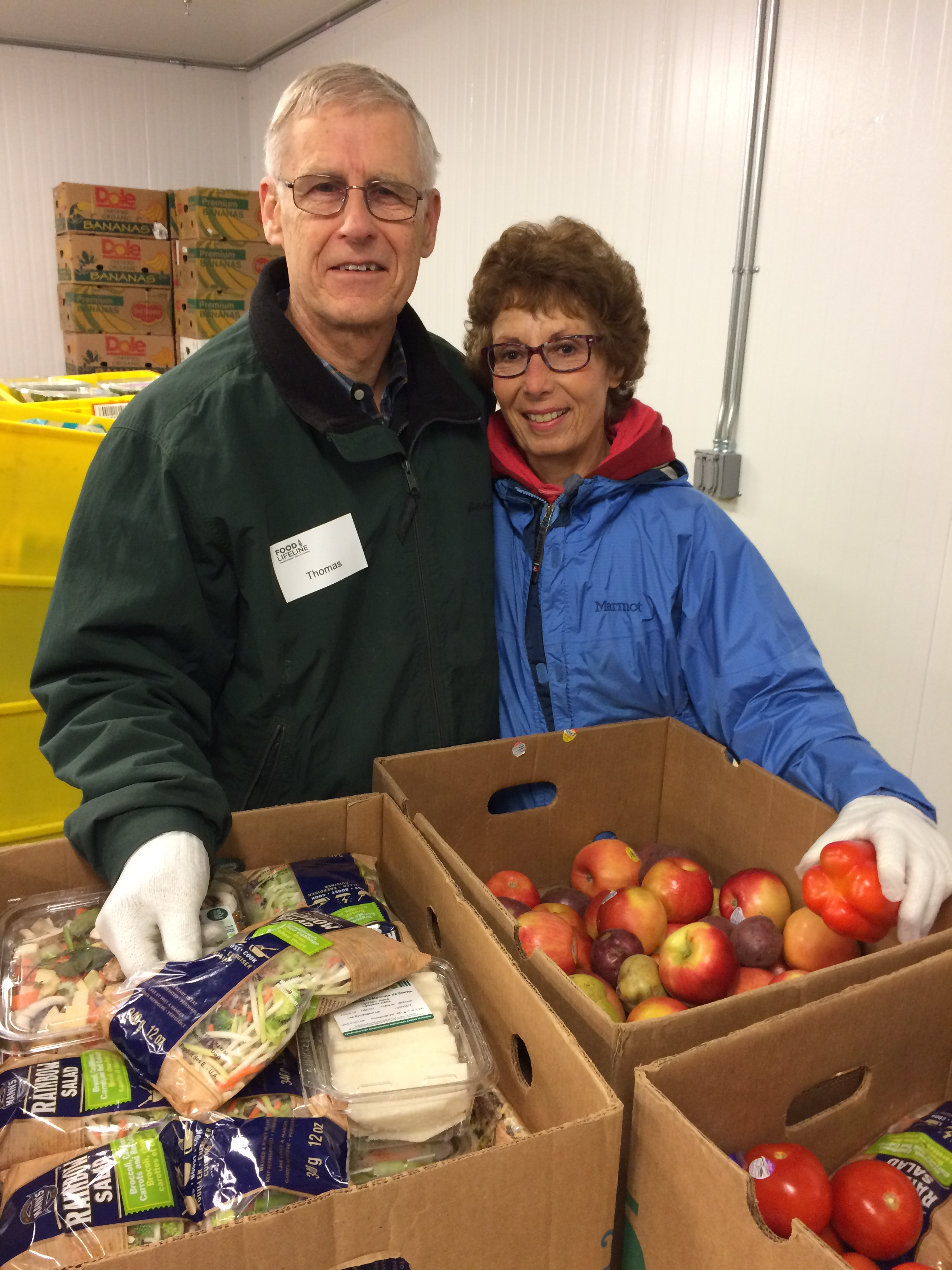 Two people, a man and a woman, smiling at the camera while sorting food