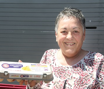 Smiling woman holding a carton of eggs