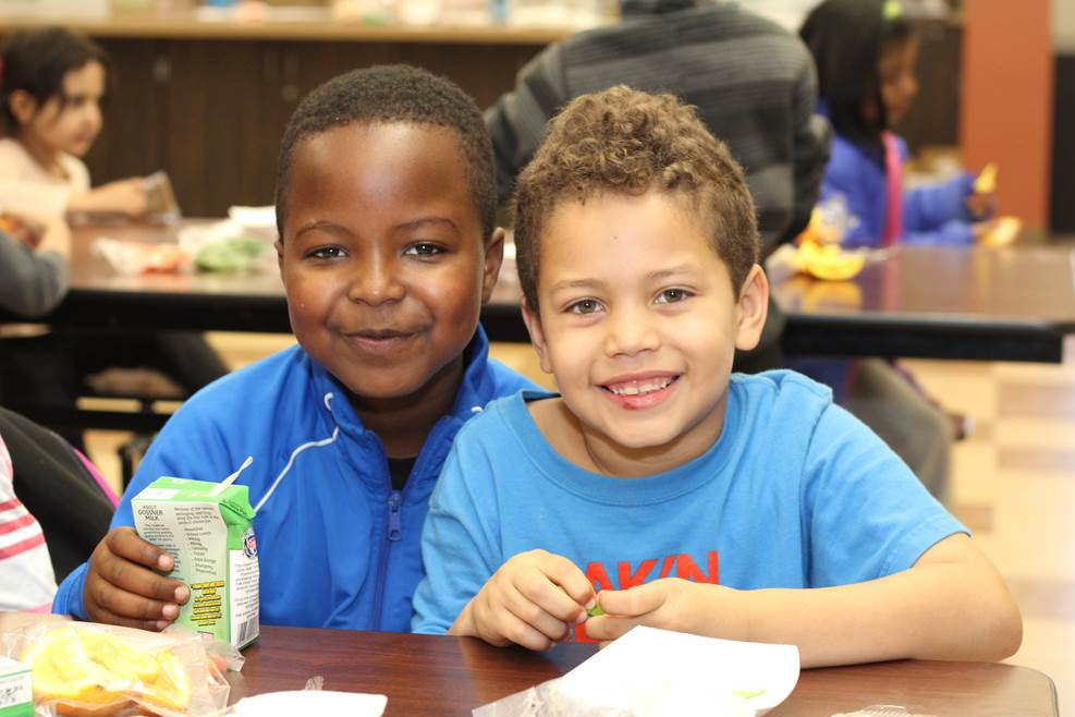 Two young boys smiling at a lunch table