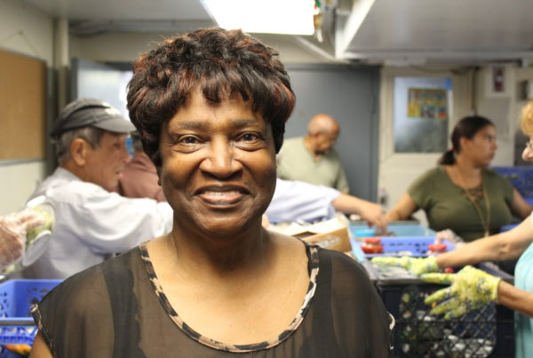 Smiling woman looks into camera during food bank distribution
