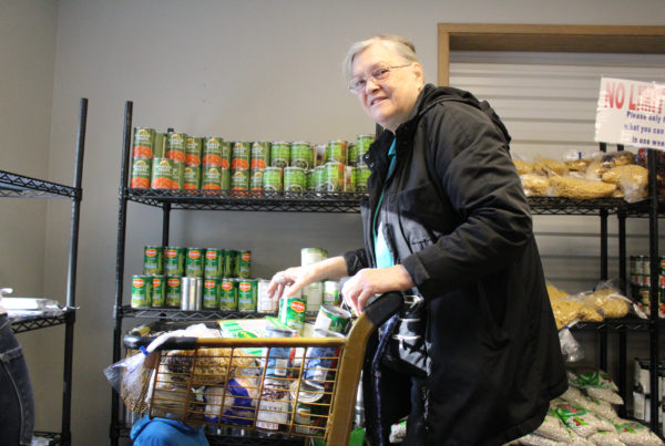 Grandma shops at local food bank. She smiles at the camera as she places canned vegetables in her cart.