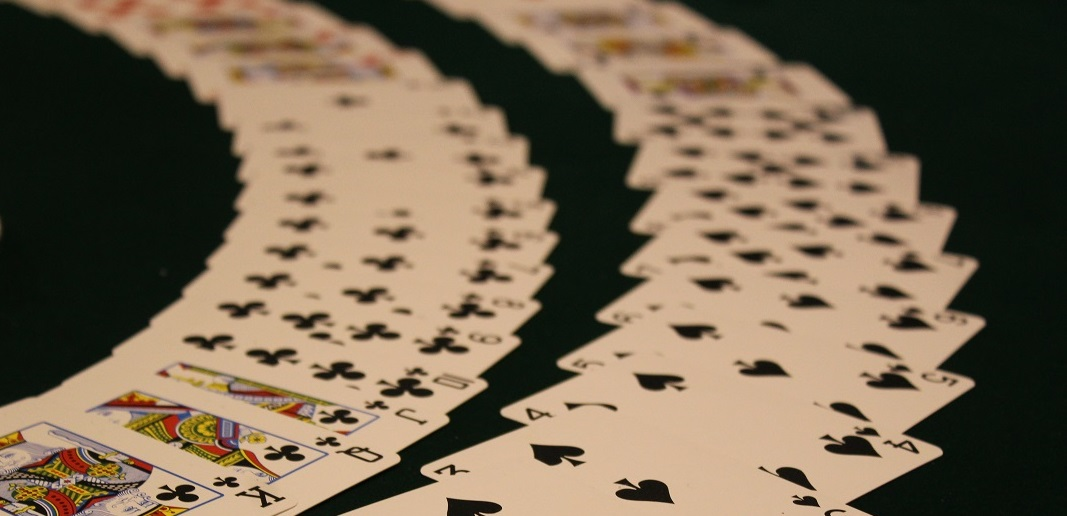 Playing cards fanned out on felt table